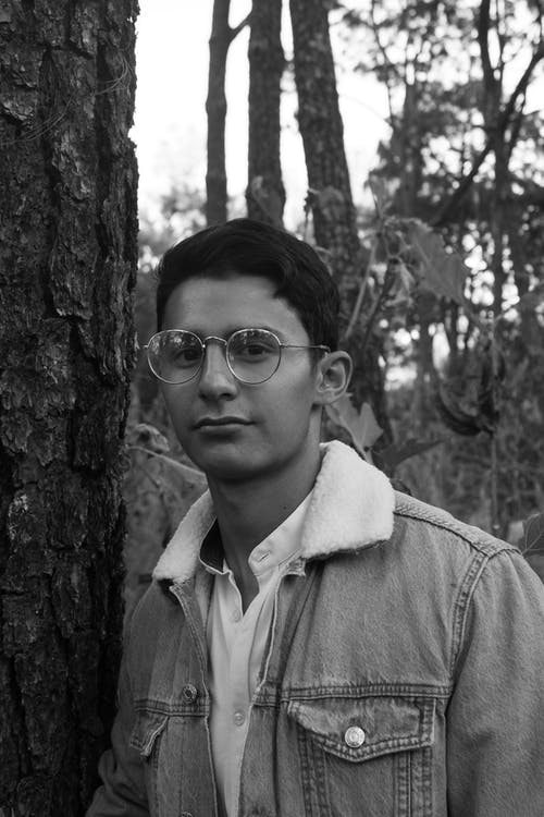 Grayscale Photo of a Man Wearing a Pair of Eyeglasses