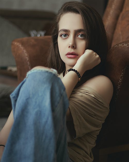 Woman in Beige Off Shoulder Top and Blue Denim Jeans Sitting Beside Brown Leather Couch