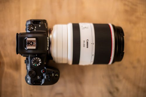 Professional photo camera with lens on wooden table
