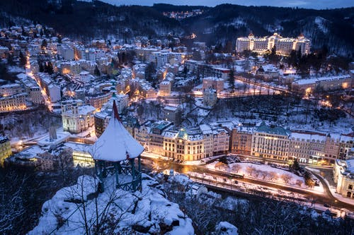 Aerial Shot of Town Covered with Snow Illuminated at Night