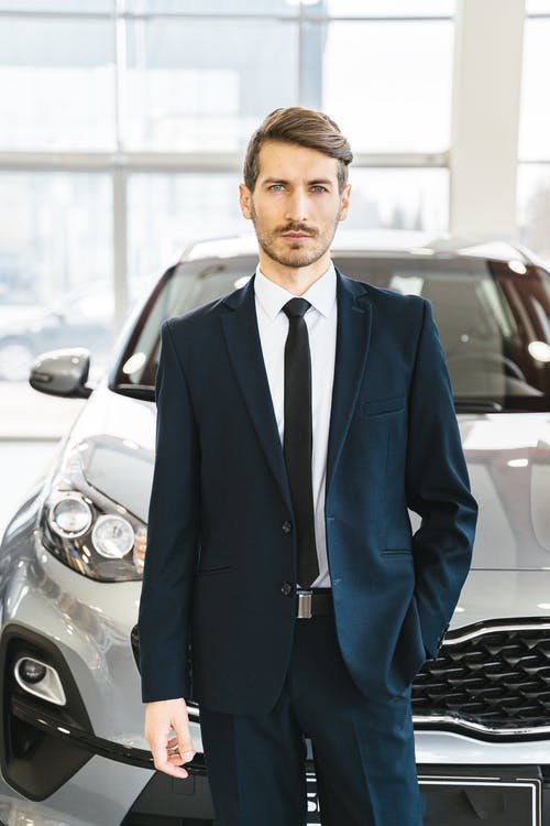 Man in Blue Business Suit Standing in Front of Car