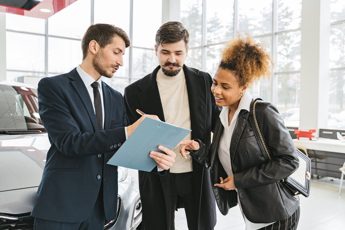 A salesperson at a dealership helping customers with FAQ about new Nissan models