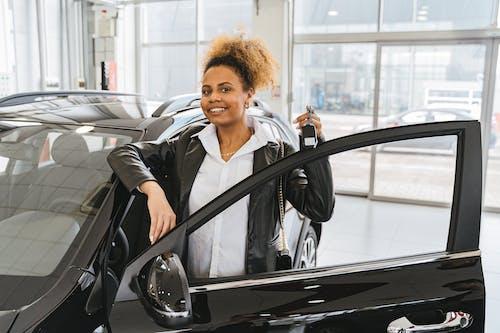 Woman in Black Blazer Standing Beside Black Car