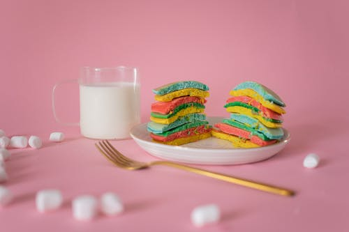 Delicious bright pancake served on plate near fork and white marshmallow on pink background