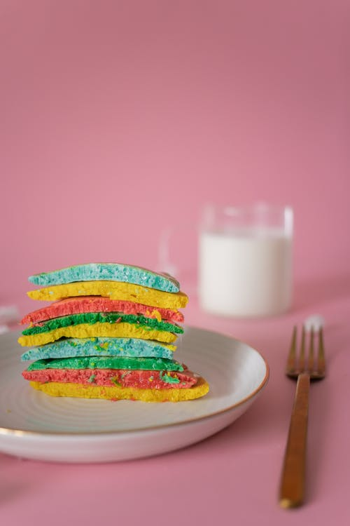 Sliced multicolored pancakes on plate near glass of milk