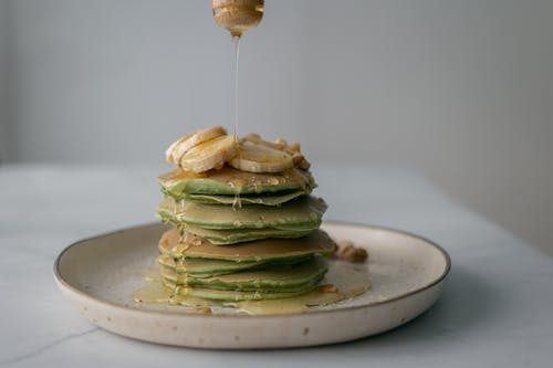 Unrecognizable person pouring honey on stack of appetizing green pancakes topped with bananas and walnuts and served on plate on table