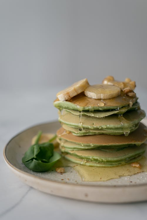 Stack of yummy healthy homemade pancakes stuffed with spinach and topped with syrup and sliced bananas on table