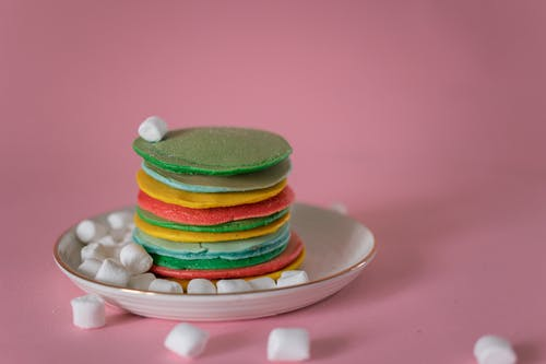 High angle of stack of multicolored appetizing pancakes stacked on plate with soft white marshmallows against pink background