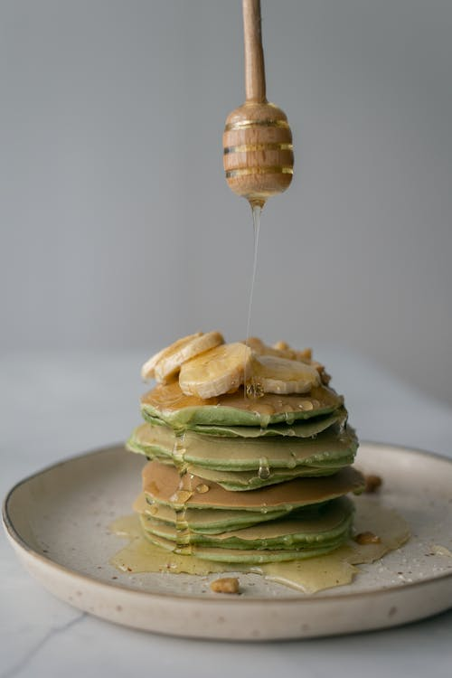 Person adding honey on pancakes with wooden dipper