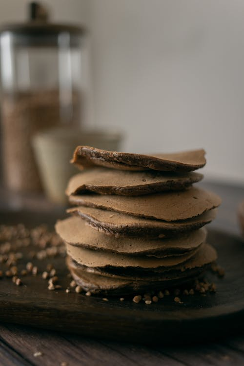 Stack of yummy chocolate pancakes on plate in kitchen
