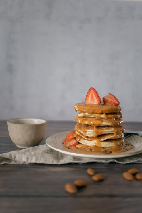 Delicious pancakes with topping near cup