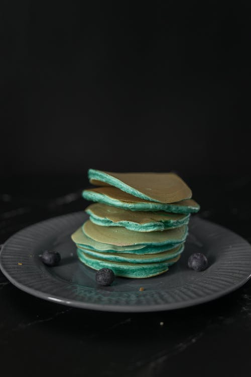 Heap of tasty blue pancakes served on round plate with scattered ripe blueberries on table against black background in modern studio
