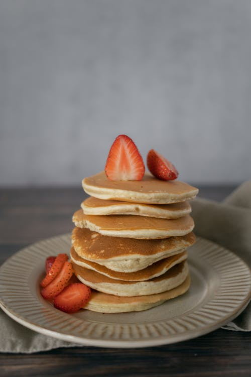 Heap of delicious pancakes served with cut fresh strawberries on white plate placed on wooden table with napkin in light kitchen