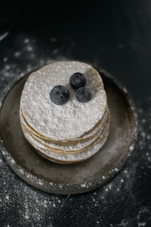 Pancakes with blueberries on table