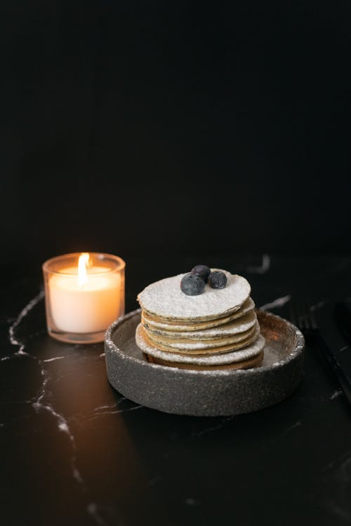 Pancakes with blueberries near candle
