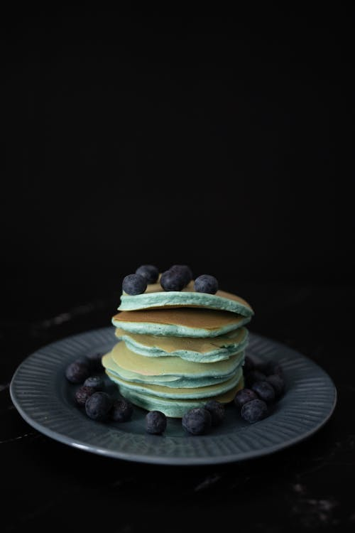 Heap of tasty pancakes topped with whole ripe blueberries served on round plate on table against black background in studio