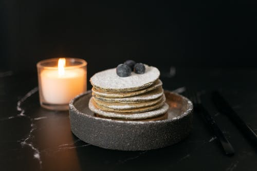 Pancakes with blueberries near candle candle on table