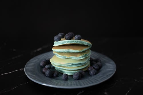 Heap of appetizing blue pancakes topped with ripe blueberries served on round plate with scattered berries against black background in studio