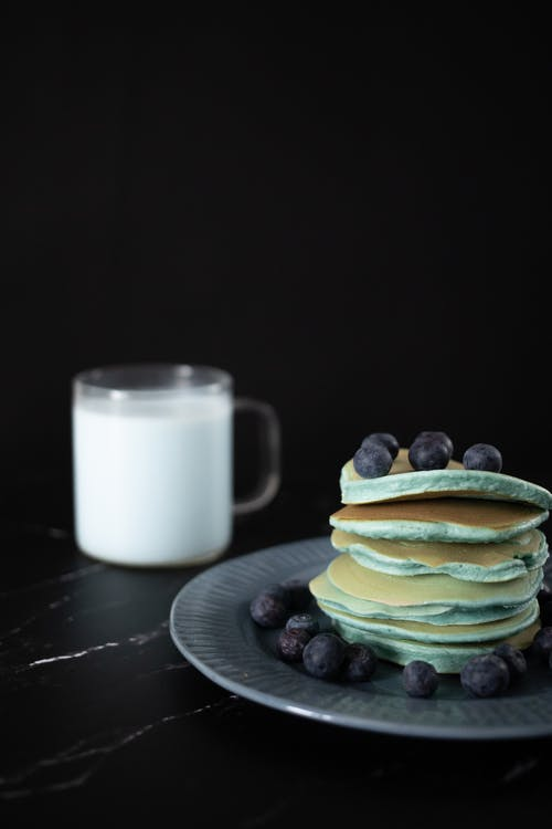 Tasty pancakes topped with blueberries served on plate near glass mug of milk on table against black background in studio