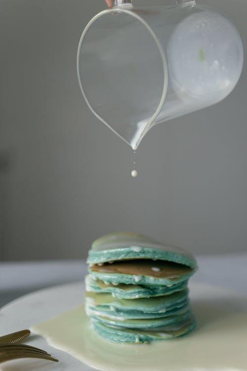 Mint pancakes poured with milk from plastic transparent jug
