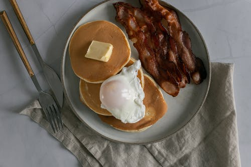 Plate with pancakes with butter near roasted bacon and poached egg
