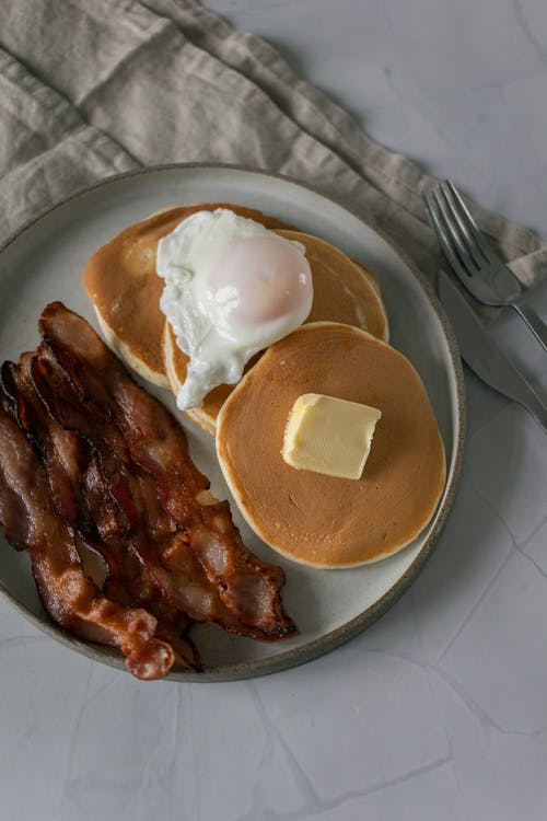 Pancakes near fried bacon slices and poached egg on plate