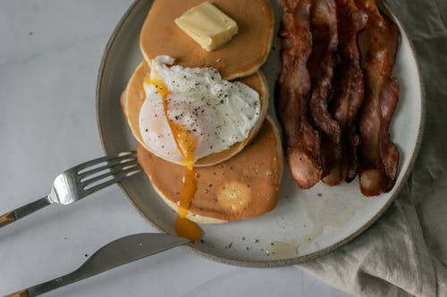 Plate with pancakes with butter near poached egg and roasted bacon