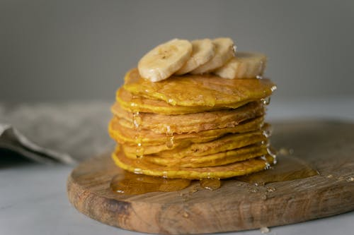 Delicious homemade pancakes covered with honey with sliced bananas placed on wooden chopping board on table in light place