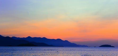 Silhouette of Mountain Beside Ocean during Orange Sunset