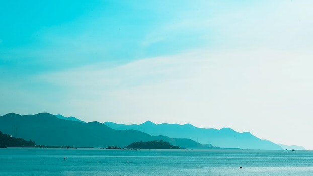 Silhouette of Mountain Near the Body of Water Photo in Daytime