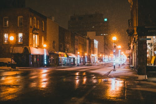 Empty asphalt road between modern buildings with glowing lights and signboards on snowy night in winter