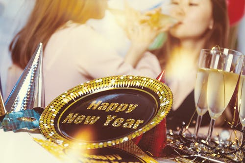 New Year party supplies on table with women drinking champagne