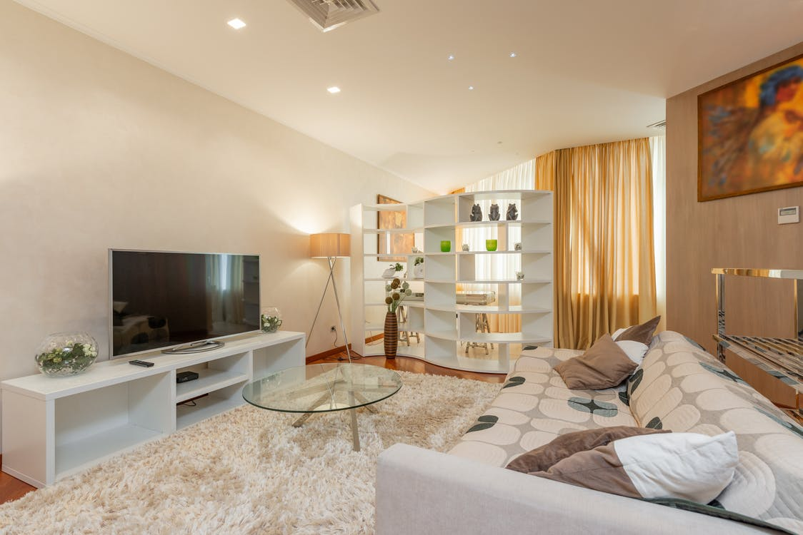 Glass round coffee table placed on soft fur rug between comfortable sofa and modern TV set in spacious living room