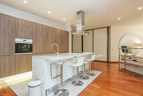 Chairs placed near white counter near wooden cupboards with built in oven in spacious modern studio apartment with kitchen and living room