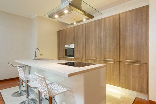 Interior of contemporary illuminated kitchen with minimalist styled furniture and built in appliances in spacious apartment