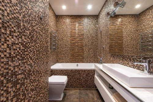 Mosaic tiled walls in modern bathroom with ceramic sink on white cabinet and bathtub