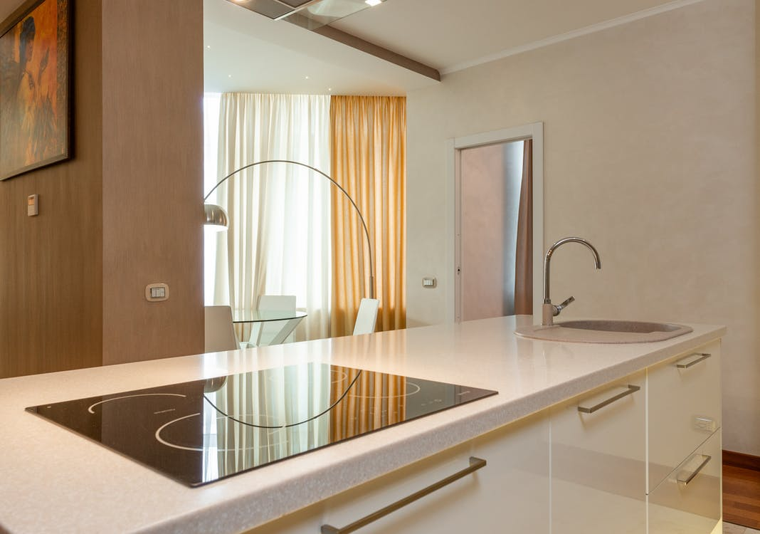Built in stove and sink with chrome faucet on counter in modern kitchen with dining area in spacious apartment