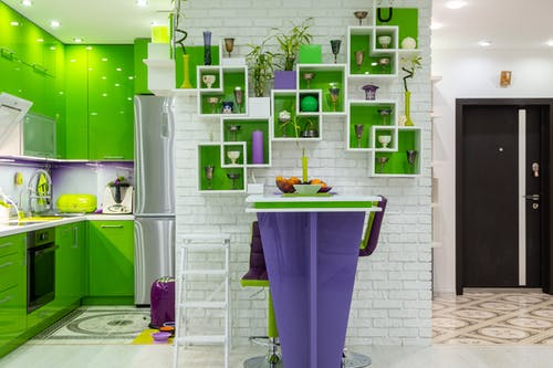 Creative shelves decorated with various vases and plants hanging on white brick wall above counter in contemporary kitchen with bright green and purple furniture