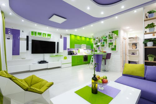 Comfy sofa with armchair and coffee table placed in front of modern TV set in spacious studio apartment near kitchen with bright green cabinets and counter