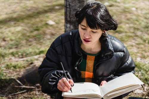 Concentrated Asian female in outerwear taking notes in workbook with pencil while sitting on grassy ground in park on sunny day