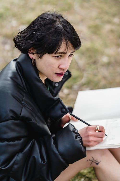 Side view of thoughtful Asian female student in jacket looking into distance with serious face while taking notes on lawn on blurred background