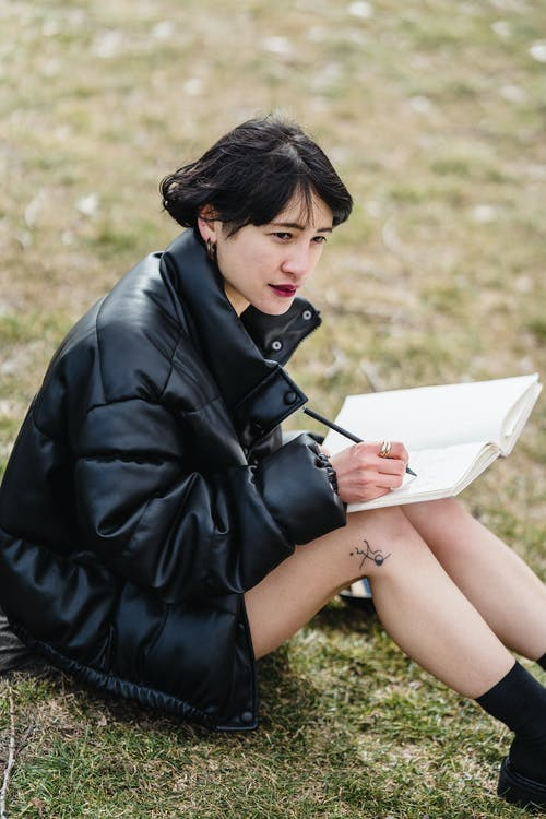 Concentrated Asian woman studying on lawn