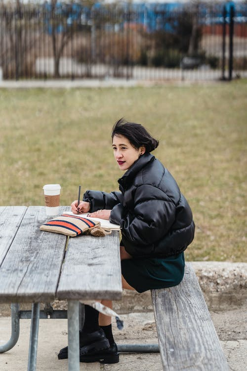 Ethnic student studying at table with coffee in park