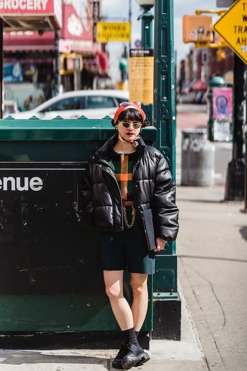 Stylish woman in headband standing on street
