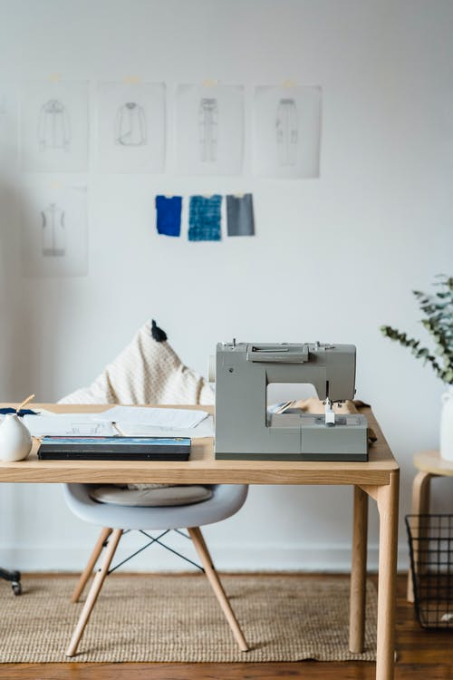 Professional sewing machine on wooden table near chair at wall with drafts of clothes and samples of textile in atelier