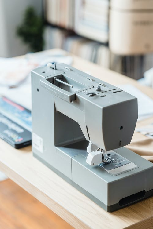 Professional gray sewing machine placed on table with sewing supplies in modern light workshop with books on bookshelves on blurred background