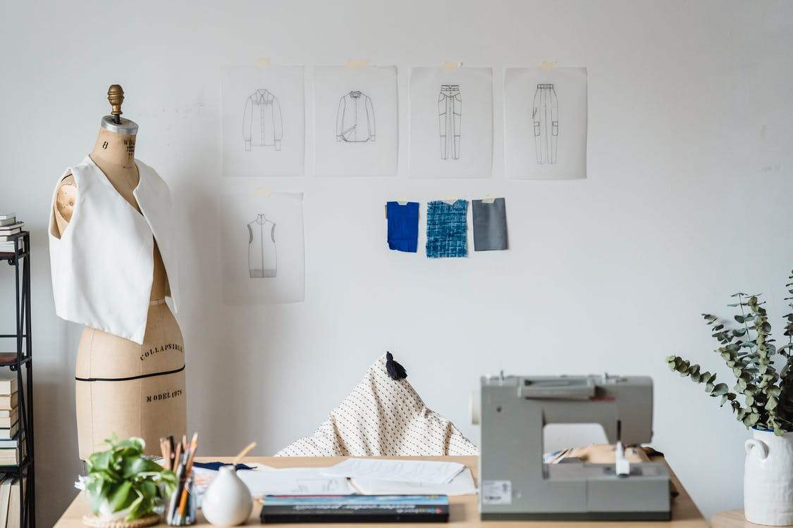 Table with sewing machine placed near mannequin with garment at white wall with drafts of cloth and samples of textile