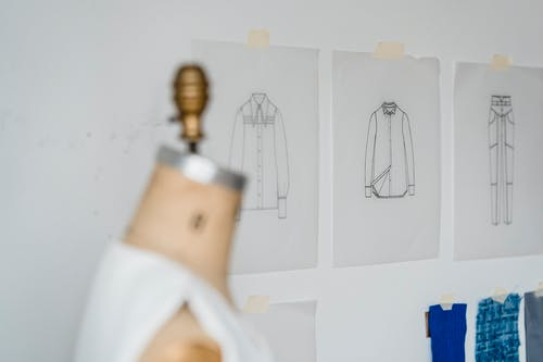 Blurred dummy placed near wall with various drafts of stylish clothes and samples of colorful textile in light modern atelier