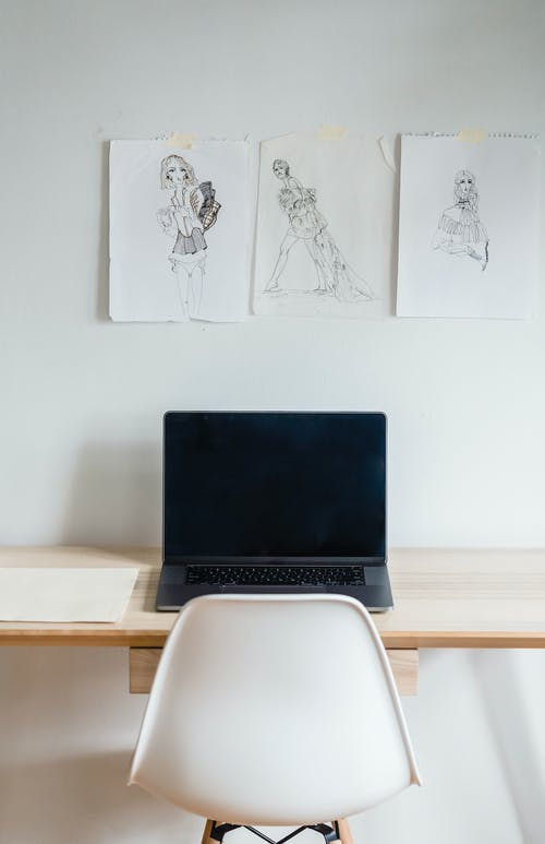 Laptop at wall with sketches in atelier