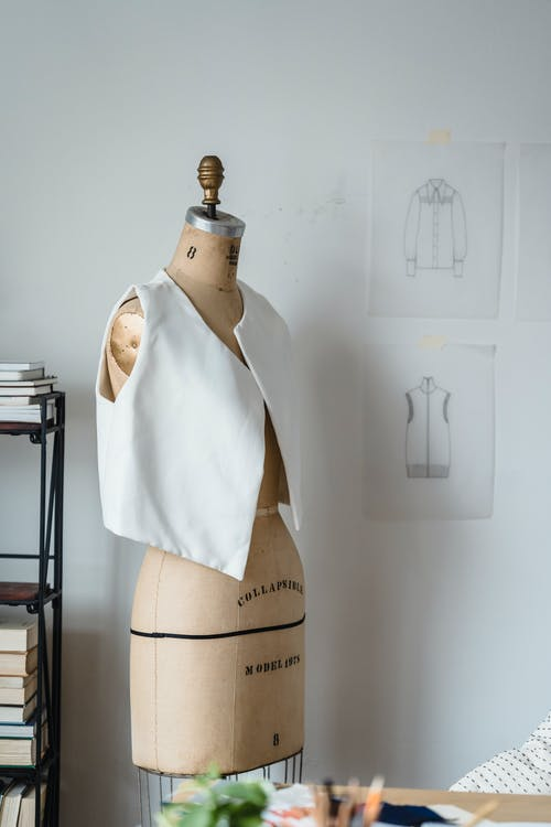 Mannequin in white vest at white wall with drafts of clothes in light room of modern atelier with books